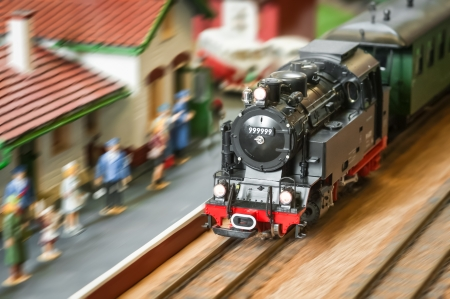 model railroad steam locomotive (with fake number) speeding through a station