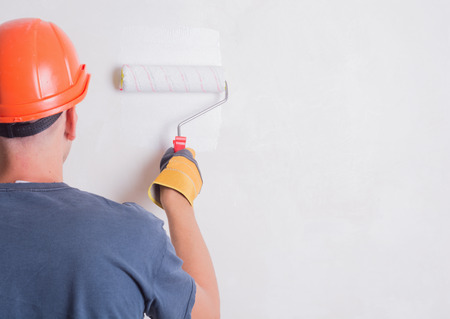 Photo for Painter On Stepladder Painting Wall With Brush - Royalty Free Image