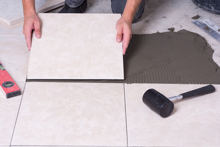 Photo for Tiler installing ceramic tiles on a floor . - Royalty Free Image