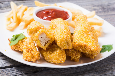Photo pour chicken strips and French fries  on rustic wooden background - image libre de droit