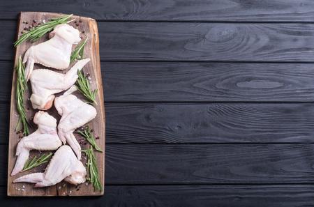 Foto de Chicken raw wings with rosemary , garlic , pepper and salt . Ingredient for preparation - Imagen libre de derechos