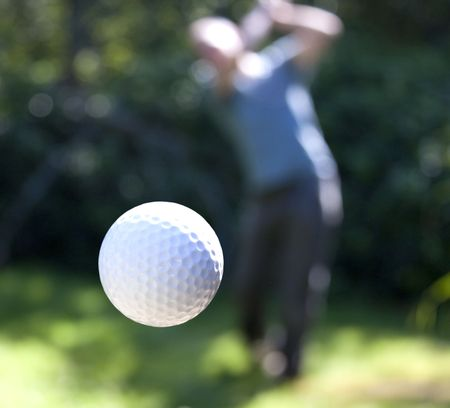 A golf ball just coming off the tee from a golfer in swing.