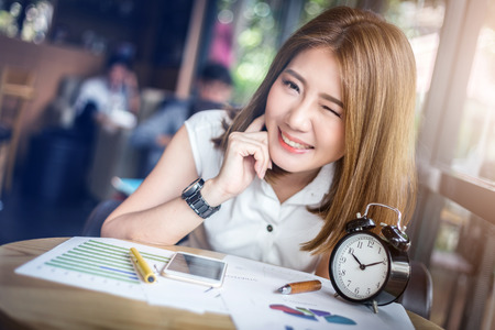 Foto de cute happy asia girl blink eye working in coffeeshop with paper graph on wooden table with light flare effect - Imagen libre de derechos