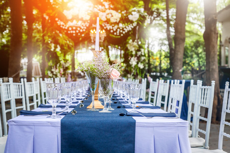 Photo for glass of vase with beautiful flowers with dining set  at a Wedding Reception with light flare effect - Royalty Free Image