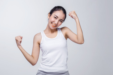 Photo pour Beautiful brunette Asian girl in white tshirt stretching, relaxing on white background - image libre de droit