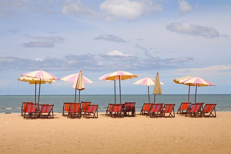 group of beach chairs with umbrella and yacht at ocean front