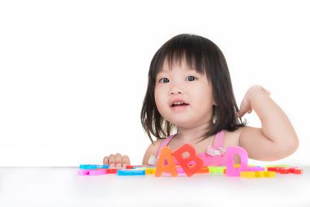 Foto de little Asian girl is playing with ABC toy - Imagen libre de derechos