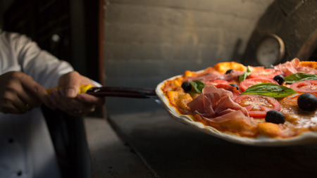 Foto per Chef put parma ham pizza in to clay stove at Italian restaurant. - Immagine Royalty Free