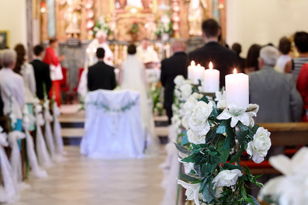 Photo for Young couple during the wedding ceremony before the altar in a church full of people - selective focus on flowers - Royalty Free Image