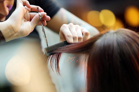 Foto de Hairdresser trimming blond hair with scissors - Imagen libre de derechos