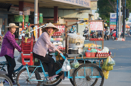 Photo pour HO CHI MINH - APRIL 19, 2015: Two unidentified local women cooks drive their bicycle carts along Truong Chinh Street to their point of work. Their business is cooking food in the street. - image libre de droit