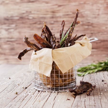 Photo pour jerked meat, cow, deer, wild beast or biltong in kraft paper bowls on a rustic table, selective focus - image libre de droit