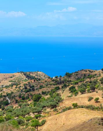 Foto de Picturesque summer view to sea and Sicily island in far from mountain hills in Motta San Giovanni outskirts, Reggio Calabria, Italy. - Imagen libre de derechos