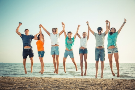 Foto de Multiethnic Group of People Jumping at Beach - Imagen libre de derechos