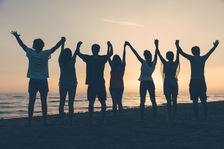 Photo pour Group of People with Raised Arms looking at Sunset - image libre de droit