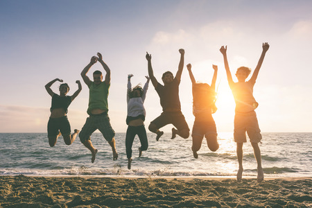 Photo for Multiracial Group of People Jumping at Beach, Backlight - Royalty Free Image