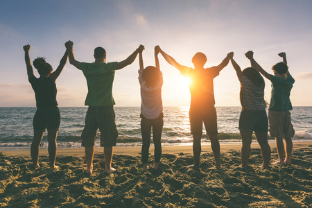 Photo for Multiracial Group of People with Raised Arms looking at Sunset - Royalty Free Image