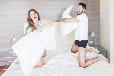 Photo pour Happy Couple Having Pillow Fight in Hotel Room - image libre de droit