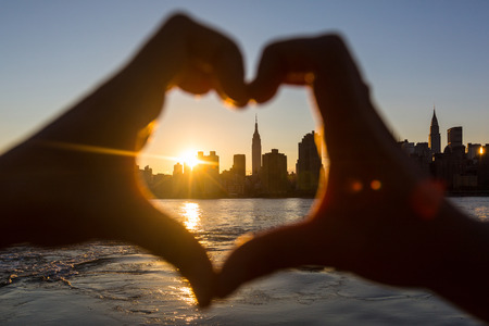 Photo for Heart Shaped Hands at Sunset, New York Skyline on Background - Royalty Free Image