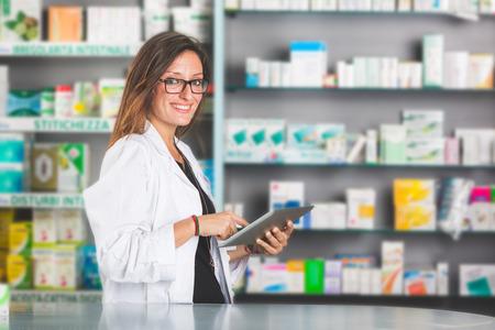 Foto de Beautiful Pharmacist with Digital Tablet in a Drugstore - Imagen libre de derechos