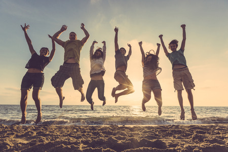 Photo pour Multiracial group of people jumping at beach. Backlight shot. Happiness, success, friendship and community concepts. - image libre de droit