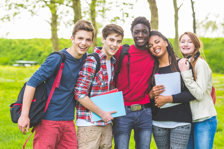 Photo for Group of multiethnic teenage students embraced together at park. Two boys and one girl are caucasian, one boy and one girl are black. Friendship, immigration, integration and multicultural concepts. - Royalty Free Image