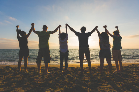 Foto de Multiracial group of people with raised arms looking at sunset. Backlight shot. Happiness, success, friendship and community concepts. - Imagen libre de derechos