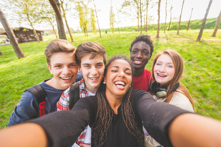 Photo pour Group of multiethnic teenagers taking a selfie at park. Two boys and one girl are caucasian, one boy and one girl are black. Friendship, immigration, integration and multicultural concepts. - image libre de droit