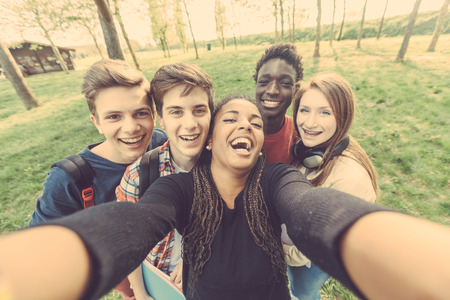 Photo for Group of multiethnic teenagers taking a selfie at park. Two boys and one girl are caucasian, one boy and one girl are black. Friendship, immigration, integration and multicultural concepts. - Royalty Free Image