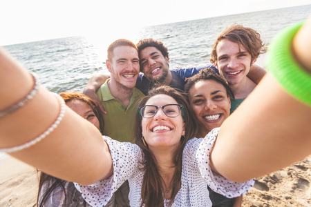 Foto de Multiracial group of friends taking selfie at beach. One girl is asiatic, two persons are black and three are caucasian. Friendship, immigration, integration and summer concepts. - Imagen libre de derechos