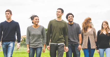 Foto de Multiethnic group of friends at park walking and enjoying time all together. Mixed race group with caucasian, black and asian people. Friendship, lifestyle, immigration concepts. - Imagen libre de derechos
