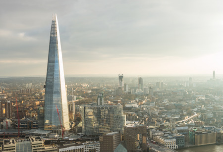 Photo pour Aerial view of London with The Shard skyscraper and Thames river at sunset with grey clouds in the sky - image libre de droit