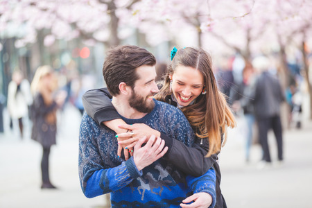 Foto de Young hipster couple embracing and smiling in Stockholm with cherry blossoms at Kungstradgarden, the swedish for Kings Garden. Love and friendship concepts with a hipster theme. - Imagen libre de derechos