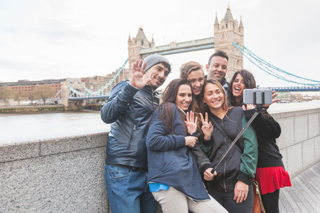 Photo pour Group of friends taking a selfie using a selfie stick in London with Tower Bridge on background. They are four girls and two boys in their twenties, embracing and having fun together. - image libre de droit