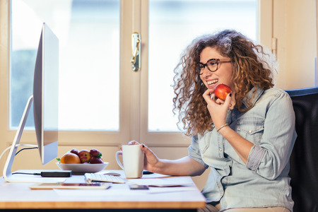 Photo pour Young woman working at home or in a small office, vintage hipster clothing, curly hair. She is eating some fresh fruits, there is a cup of tea or coffee on the desk with some technological devices. - image libre de droit