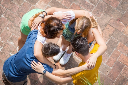 Photo pour Group of teenagers embraced in circle, aerial view. They are two girls and two boys, looking each other - image libre de droit
