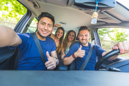 Photo pour Group of friends taking a selfie into the car before leaving for vacations. They are a mixed race group of four persons, two caucasian and two hispanic. - image libre de droit
