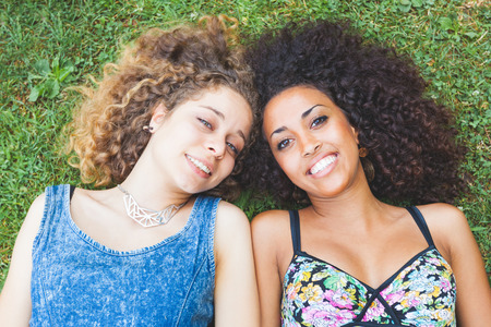 A multiracial couple of women lying on the grass. They are two young women resting at park. One is caucasian blonde and the other is black brunette, both have curly hair. They are smiling and wearing summer clothes.