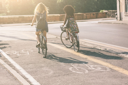 Foto de Couple of female friends riding bikes on the street. Focus on bike icon. They are two women wearing summer clothes are riding bikes. They are on the cycle track along a city road. - Imagen libre de derechos