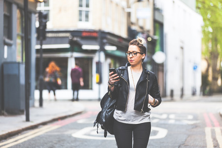 Photo pour Girl walking down the street with her phone. A woman is walking alone in London. She is looking at her smart phone. Blurred on background there are  typical english houses and shops. - image libre de droit