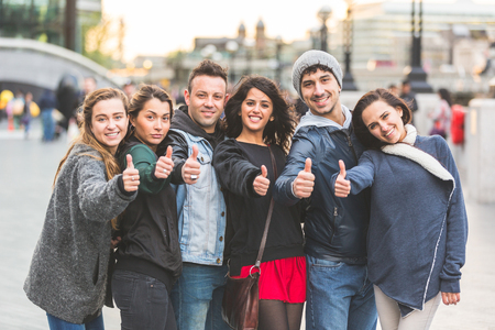 Photo for Successful group of friends showing thumbs upin London. They are four women and two men in their twenties, they are standing in a row, all very close by each other. Friendship and lifestyle concepts. - Royalty Free Image