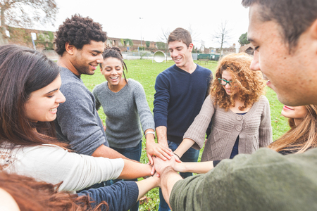 Foto de Multiracial group of friends with hands in stack, strong concept about teamwork and cooperation, also refers to immigration and friendship. - Imagen libre de derechos