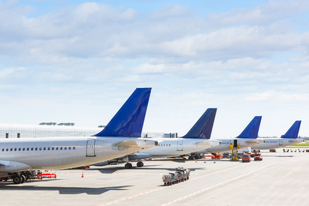 Foto de Tails of some airplanes at airport during boarding operations. They are four planes on a sunny day, with a blue sky. Travel and transportation concepts. - Imagen libre de derechos