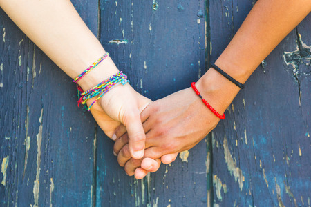 Foto de Two women holding hands with a wooden background. One is caucasian, the other is black. Multicultural, homosexual love and friendship concepts. - Imagen libre de derechos