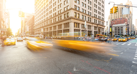 Foto de Busy road intersection in Manhattan, New York, at sunset. There are some blurred yellow cabs on foreground, and buildings, people and cars on background. Long exposure shot. Travel and city life. - Imagen libre de derechos