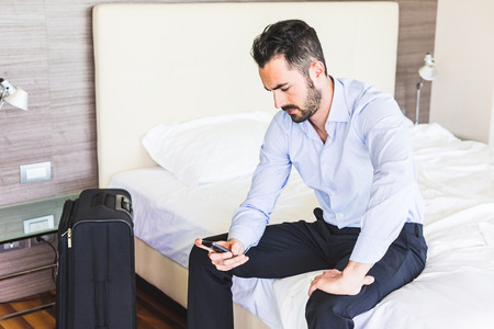 Photo for Businessman looking at smart phone in his hotel room. He is sitting on the bed, wearing black trousers and a light blue shirt. Grave expression, business and work issues concepts. - Royalty Free Image