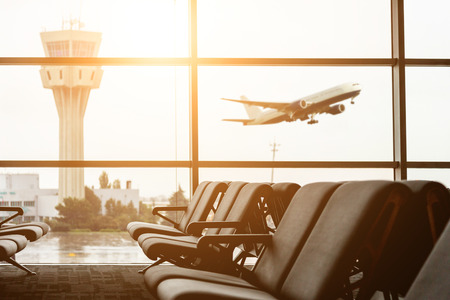 Photo for Empty chairs in the departure hall at airport , with the control tower and an airplane taking off at sunset. Travel and transportation concepts. - Royalty Free Image