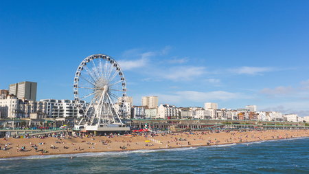 Photo for Brighton view of seaside from the pier. Panoramic shot with the famous ferris wheel, the stones beach with unrecognizable persons on a sunny summer day. - Royalty Free Image