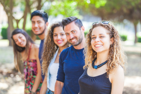 Photo for Multicultural group of friends at park. There are three women and two men smiling and looking at camera. They are wearing summer clothes. Selective focus on the girl in foreground. - Royalty Free Image