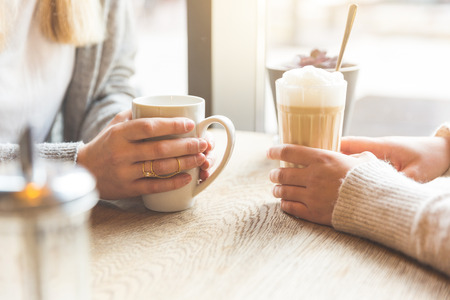 Photo for Two beautiful young women in a cafe, drinking coffee and latte macchiato. Close up shot on the hands holding the mugs. - Royalty Free Image